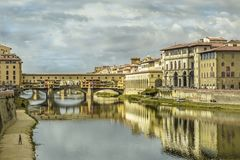 Florence pontevecchio bridge in a cloudy autumn morning. With historical medieval palace reflecting on the river water Royalty Free Stock Images