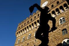 Florence som är bakbelyst av Perseus bronser med Palazzo Vecchio i bakgrunden arkivbild