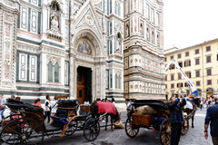 Typical horse-drawn carriages on the main facade of the cathedral of Florence `Duomo` called `Santa Maria del Fiore` stock photo