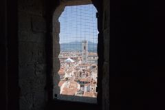 Florencki pejzaż miejski z czerwień dachów i Giotto ` s dzwonnicą Widok od wąskiego okno z żelazną siatką Palazzo Vecchio wierza, Fotografia Stock