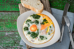 Florentine eggs with pureed spinach on the old wooden board Stock Image