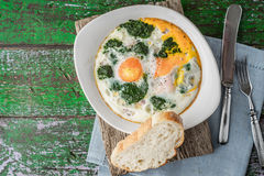 Florentine eggs with pureed spinach on the wooden table horizontal. Florentine eggs with pureed spinach on the old wooden table top view horizontal Stock Photos