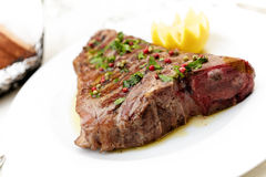 Florentine steak. Florentine style steak with lemon on white stock image