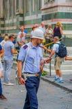 FLORENZ, ITALIEN - 12. JUNI 2015: Hübsche italienische Polizei, welche die Straße betrachtet seinen Handy kreuzt Lizenzfreies Stockfoto