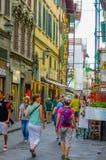 FLORENZ, ITALIEN - 12. JUNI 2015: Touristen und Leute, die in eine comercial Straße, Lose Shops auf den Seiten kreuzen A Stockfotos