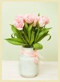 Florero blanco con un ramo de tulipanes rosados Foto de archivo libre de regalías