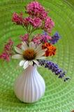 Florero blanco en la estera verde con la maravilla, valeriana, lavanda, Coneflower blanco Imágenes de archivo libres de regalías