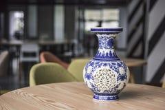 Florero a cielo abierto de la porcelana colocado en una tabla de madera redonda imagenes de archivo