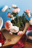 Florero con las flores del rosa y blancas en la tabla en una cocina azul fotos de archivo libres de regalías