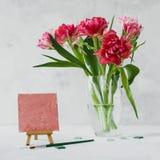 Florero con las flores del tulipán, la brocha con color en una pintura de la lona y el mosaico en backround gris imagenes de archivo