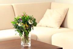 Florero con las flores en sala de estar Imagen de archivo
