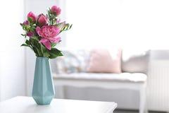 Florero con las flores hermosas de la peonía en la tabla foto de archivo
