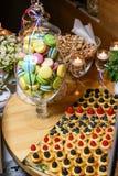 Florero con las galletas multicoloras de los macarrones con las bayas frescas del bosque, palomitas en la tabla festiva en un res Imagenes de archivo