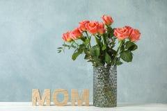 Florero con las rosas y la mamá anaranjadas de la inscripción en la tabla blanca contra fondo ligero fotos de archivo libres de regalías