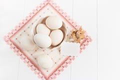 Florero con los huevos y servilleta en un fondo blanco Foco selectivo, imagen entonada, efecto de la película, visión superior Fotografía de archivo