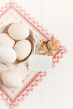 Florero con los huevos y servilleta en un fondo blanco Foco selectivo, imagen entonada, efecto de la película, visión superior Foto de archivo libre de regalías