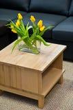 Florero con los tulipanes amarillos en la mesa de centro de madera moderna foto de archivo libre de regalías