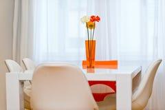 Florero con tres flores del gerbera en la tabla en comedor Foto de archivo libre de regalías