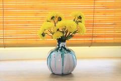 Florero de cerámica con las flores amarillas imagen de archivo