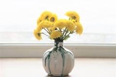 Florero de cerámica con las flores amarillas fotos de archivo libres de regalías