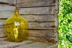 Florero de cristal amarillo en un exterior de madera de la casa Fotos de archivo