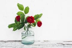 Florero de cristal con el ramo de rosas en la tabla del vintage Imagen de archivo libre de regalías