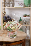 Florero de cristal con el ramo mezclado en la tabla de madera vida hermosa todavía de las flores frescas Foto de archivo libre de regalías
