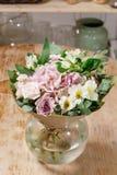 Florero de cristal con el ramo mezclado en la tabla de madera vida hermosa todavía de las flores frescas Imagen de archivo libre de regalías