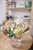 Florero de cristal con el ramo mezclado en la tabla de madera vida hermosa todavía de las flores frescas Fotografía de archivo
