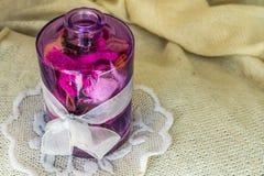 Florero de cristal con flores secadas y un arco blanco Imagenes de archivo