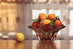 Florero de cristal con las frutas cítricas. Imagen de archivo