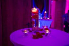 Florero de cristal con las velas del agua y de la luz de rosas rojas Imagenes de archivo