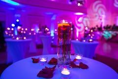 Florero de cristal con las velas del agua y de la luz de rosas rojas Foto de archivo libre de regalías