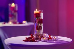 Florero de cristal con las velas del agua y de la luz de rosas rojas Imagen de archivo libre de regalías