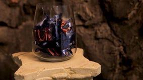 Florero de cristal con los chocolates y caramelo y velas ardientes en el primero plano Dulces del chocolate en un florero y un bu fotos de archivo
