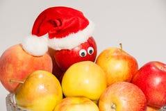 Florero de cristal de frutas con las cajas y el sombrero de la Navidad Imágenes de archivo libres de regalías
