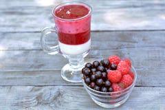 Florero de cristal por completo de la frambuesa roja y de la zarzamora fragantes cerca del yogur sabroso con las bayas mezcladas Imagen de archivo libre de regalías