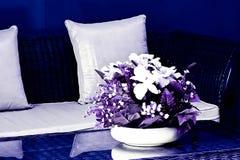Florero de flores en la tabla en la sala de estar con las paredes rojas fotografía de archivo libre de regalías