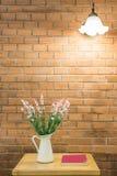 Florero de la flor y del libro en la tabla con caída ligera en la pared Imagen de archivo libre de regalías