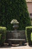 Florero de piedra antiguo con las flores en un jardín Fotografía de archivo libre de regalías