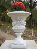 Florero de piedra en el viejo estilo clásico con las flores en el parque Imagenes de archivo