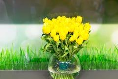 Florero de tulipanes amarillos en sala de estar moderna Fotografía de archivo libre de regalías