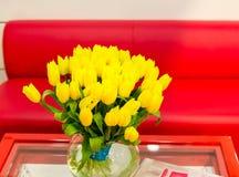 Florero de tulipanes amarillos en sala de estar moderna Imagen de archivo libre de regalías