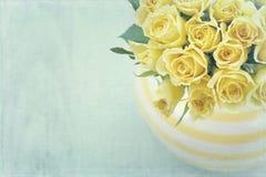Florero rayado con un ramo de rosas amarillas Imagen de archivo libre de regalías