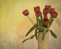 Florero texturizado sucio de tulipanes de color rosa oscuro en un florero rústico foto de archivo