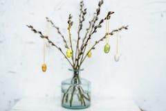 Florero transparente con las ramas adornadas con los huevos de madera para pascua Imagen de archivo