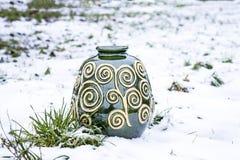 Florero verde de la arcilla en la nieve Fotos de archivo libres de regalías