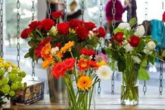 Floreros con diversas flores Fotos de archivo