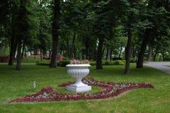 Floreros con las flores en el parque Imágenes de archivo libres de regalías