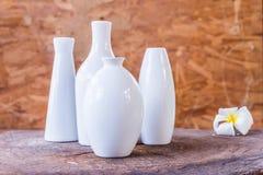 Floreros de la porcelana de diversas formas en el fondo de madera Imagenes de archivo